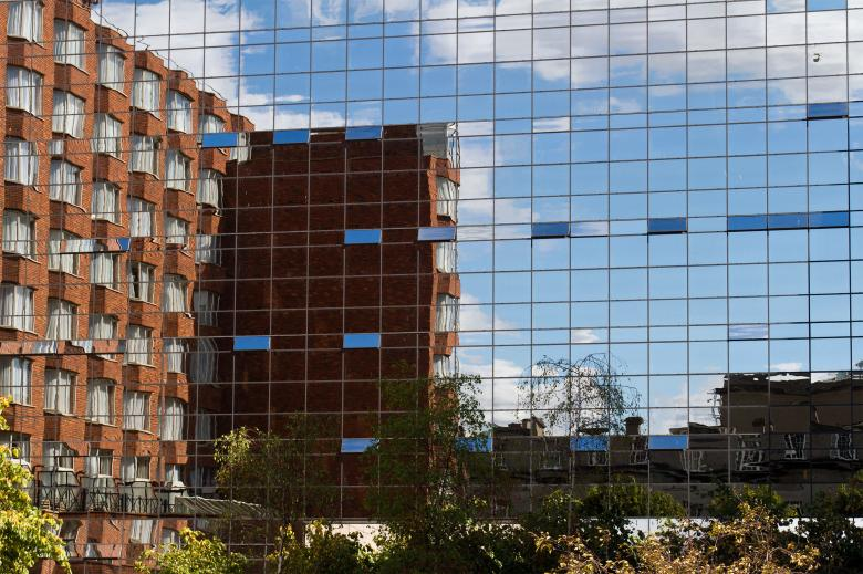 Free Stock Photo of Brick Building in Glass Building Reflection Created by Geoffrey Whiteway