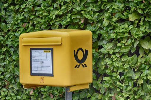 Yellow Postbox on green background of leaves - Free Stock Photo