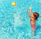 Free Photo - Little Girl Playing with a Ball in the Swimming Pool