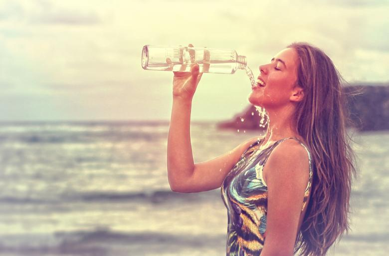 Free Stock Photo of Young Woman Drinking Sparkling Water at the Beach
