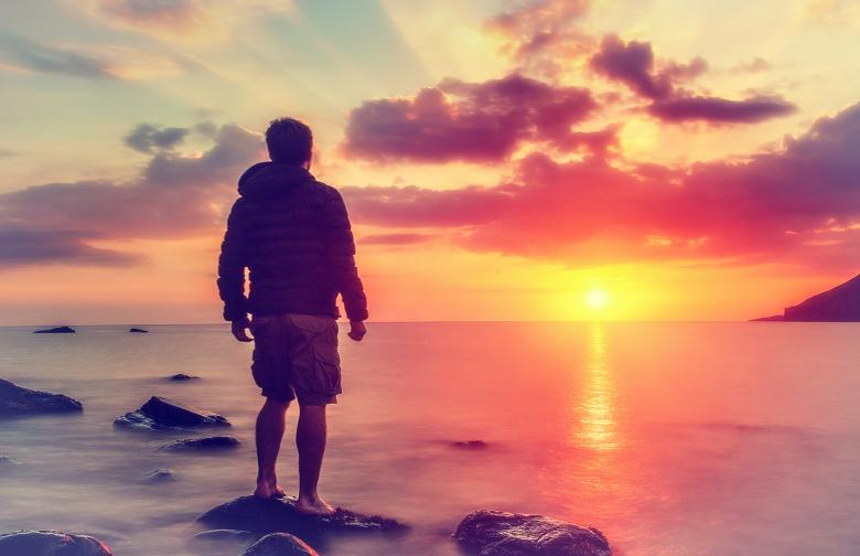 young man watching the sunrise at rocky beach free stock photo by