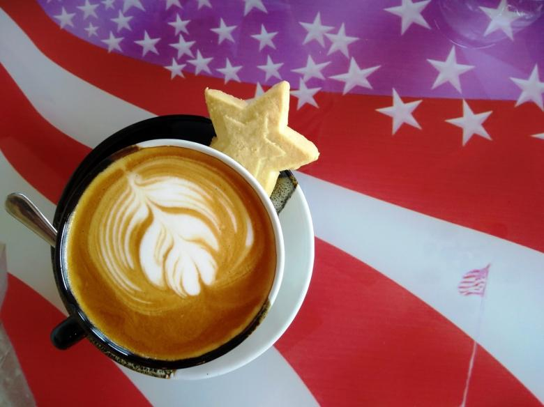 Free Stock Photo of Hot Coffee with Froth Art Against an American Stars and Stripes Flag Created by Ivan